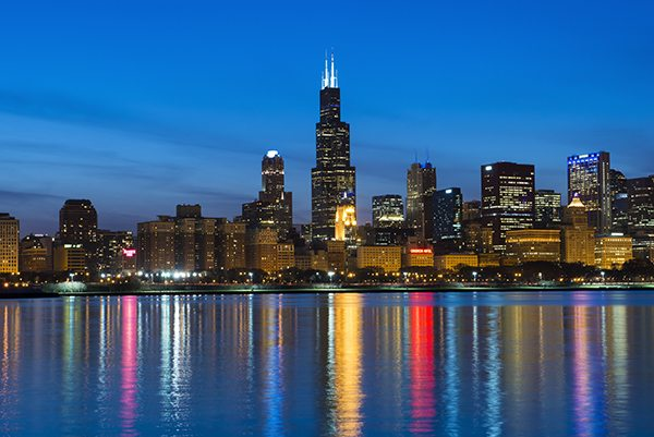 Nighttime Chicago skyline with colorful reflection in the water